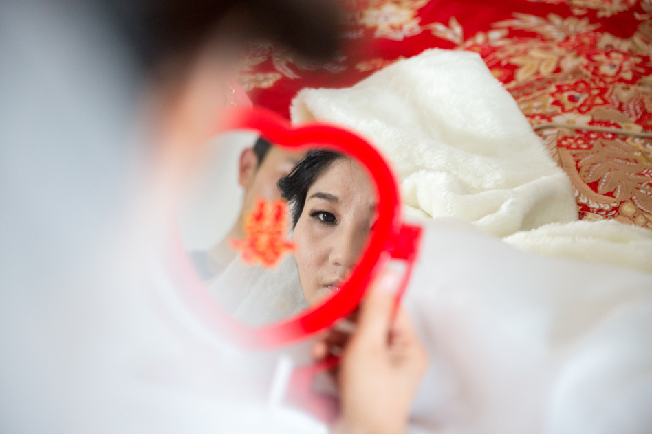 "Wang looks in a heart-shaped mirror embossed with the Chinese character xi — meaning ""double happiness."" (Sim Chi Yin for NPR)"