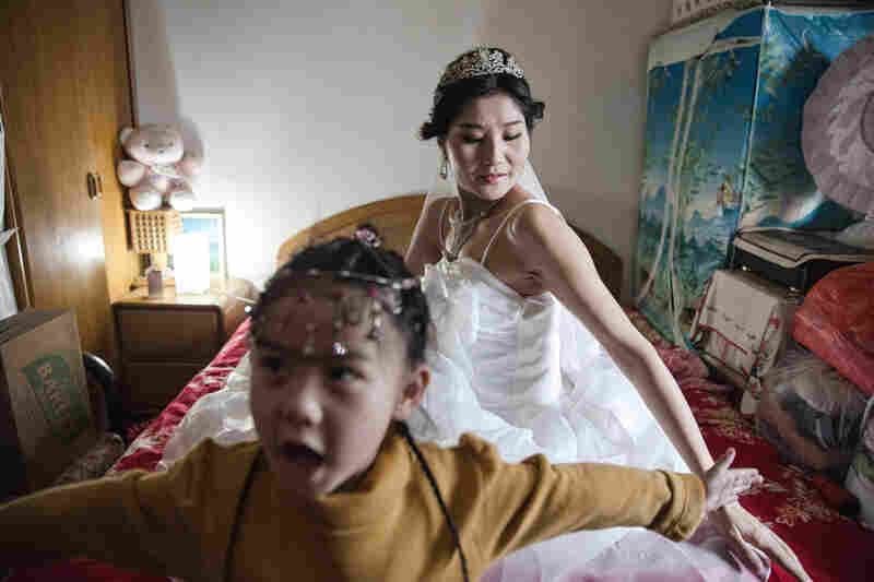 Wang's niece tries to shield her from Wei as part of traditional games played when the groom picks up the bride before their wedding ceremony.