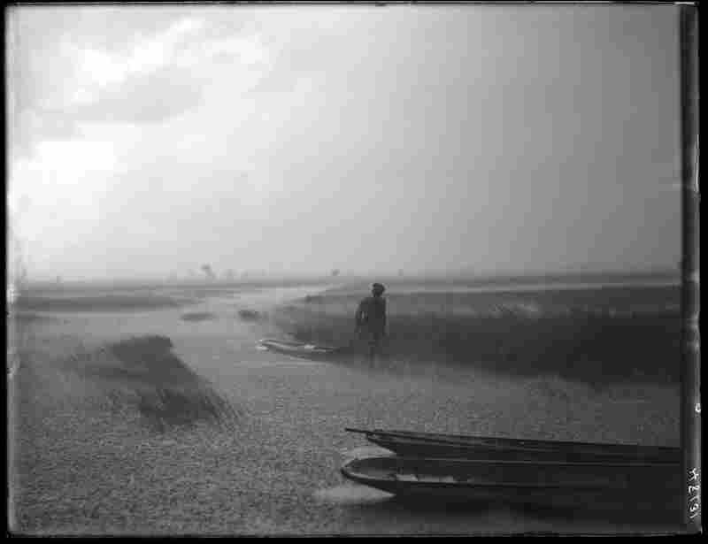 Seminole men haul a canoe in rain.