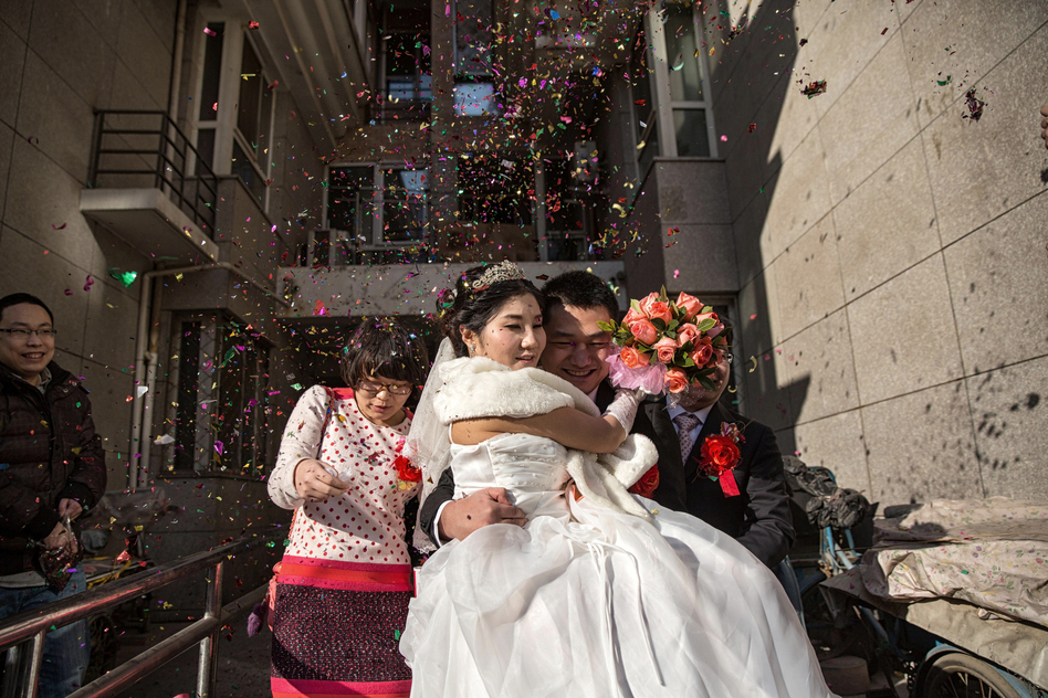 Wei carries Wang out of her apartment to a waiting entourage of six Mercedes Benzs and Audis for the drive to their wedding ceremony at a Beijing restaurant. (Sim Chi Yin for NPR)