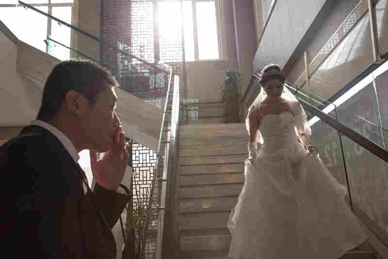 Wei smokes a cigarette as his Wang comes down the stairs for their wedding.