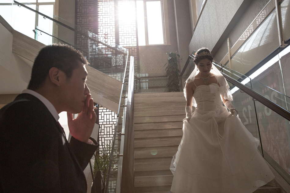 Wei smokes a cigarette as his Wang comes down the stairs for their wedding. (Sim Chi Yin for NPR)
