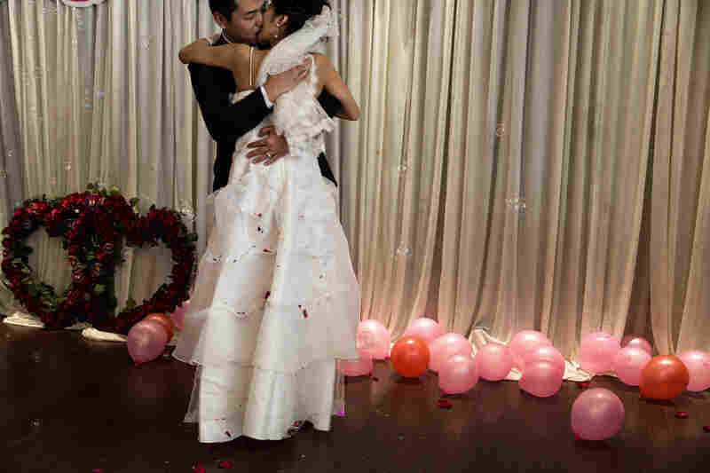 After exchanging vows and wedding rings, the couple shares kisses after being egged on by their guests.
