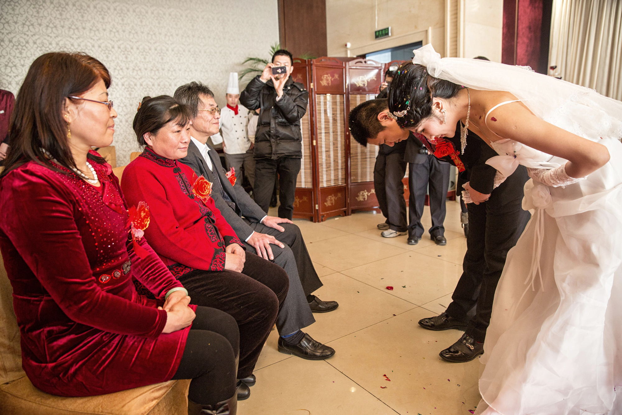 The couple bows before their parents and offers them tea, as is traditional in Chinese weddings.