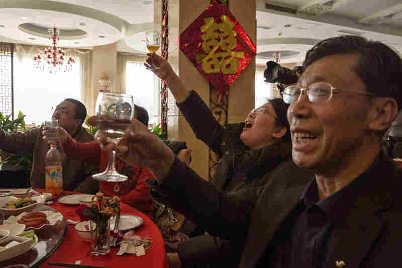 Guests raise their glasses for a toast to the newlyweds.