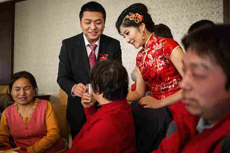 Wang and Wei go from table to table to toast their guests. Wei had to borrow money to pay Wang's bride price and is counting on his parents to give them an apartment to live in.