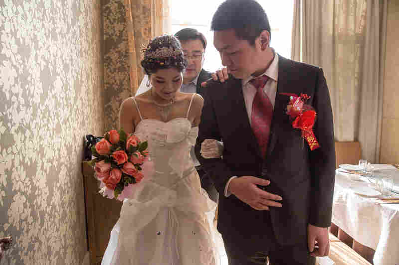 Wang and Wei practice walking down the aisle, just before their wedding ceremony at a Beijing restaurant.