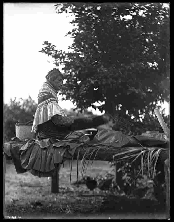 A Seminole woman sifts cornmeal.