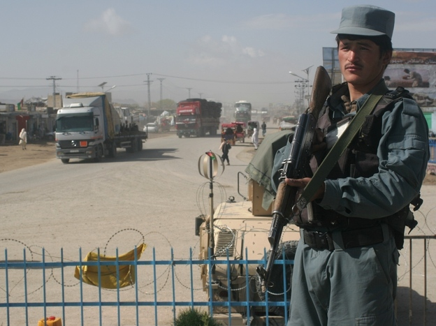 An Afghan police officer stands guard near the site where a suicide bomb attack took the life of five Americans, including 25-year-old Foreign Service officer Anne Smedinghoff, in Afghanistan on Saturday.