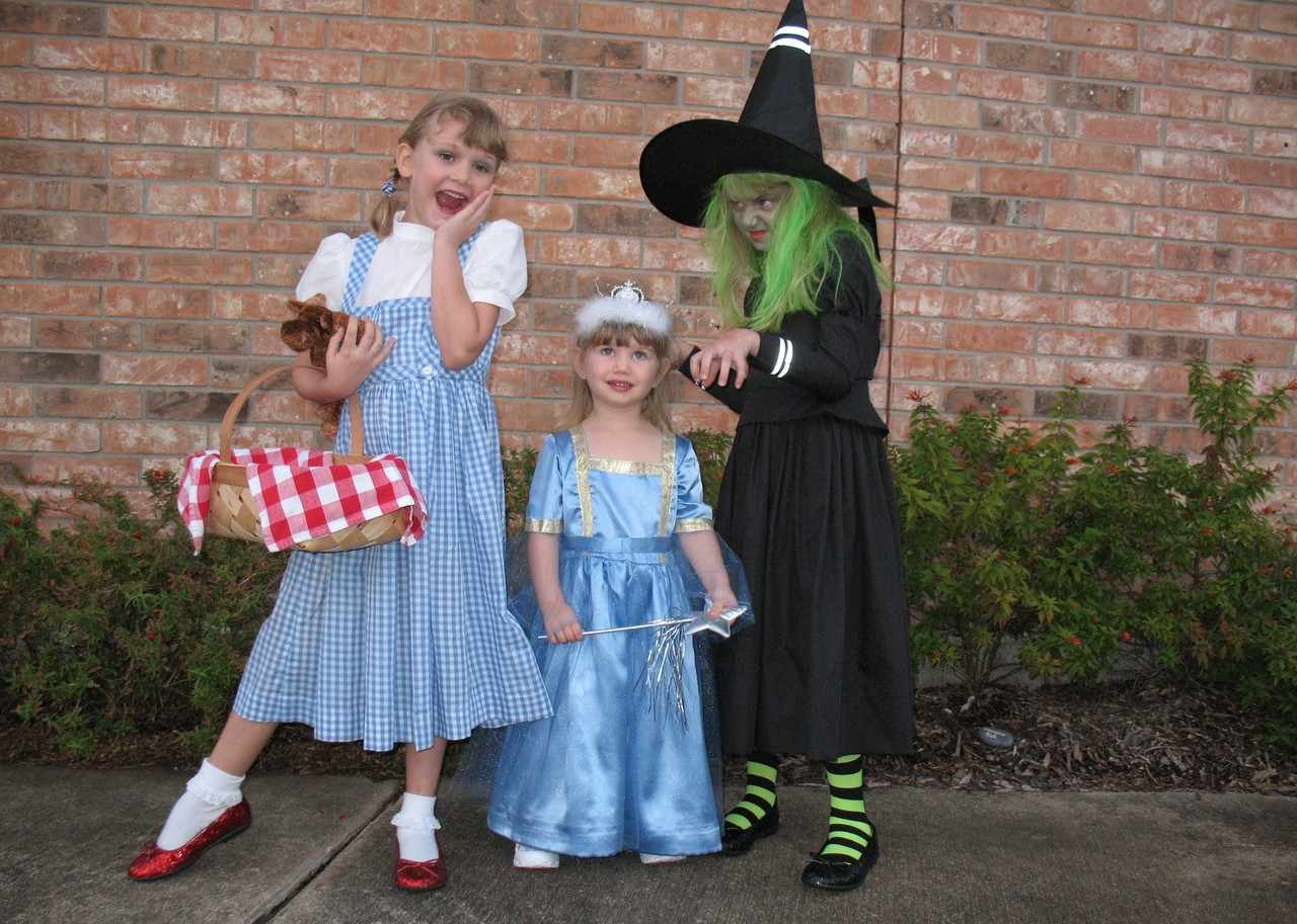 """Halloween 2009, Houston -- there's Kathryn as Dorothy with her little moose named Toto (we didn't have a stuffed dog) and 2-year-old Eliza as a very tiny Good Witch Glinda, plus Phoebe as the Wickedest Witch of the West. The gorgeous costumes were handmade by my mother-in-law."" -- Brenda Lightfoot"