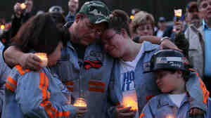 In this 2010 photo, coal miner Terry Cooper, left, embraces his wife Michelle, daughter Tera and son Justin, during a vigil to honor the coal miners that were killed in Montcoal, W. Va.