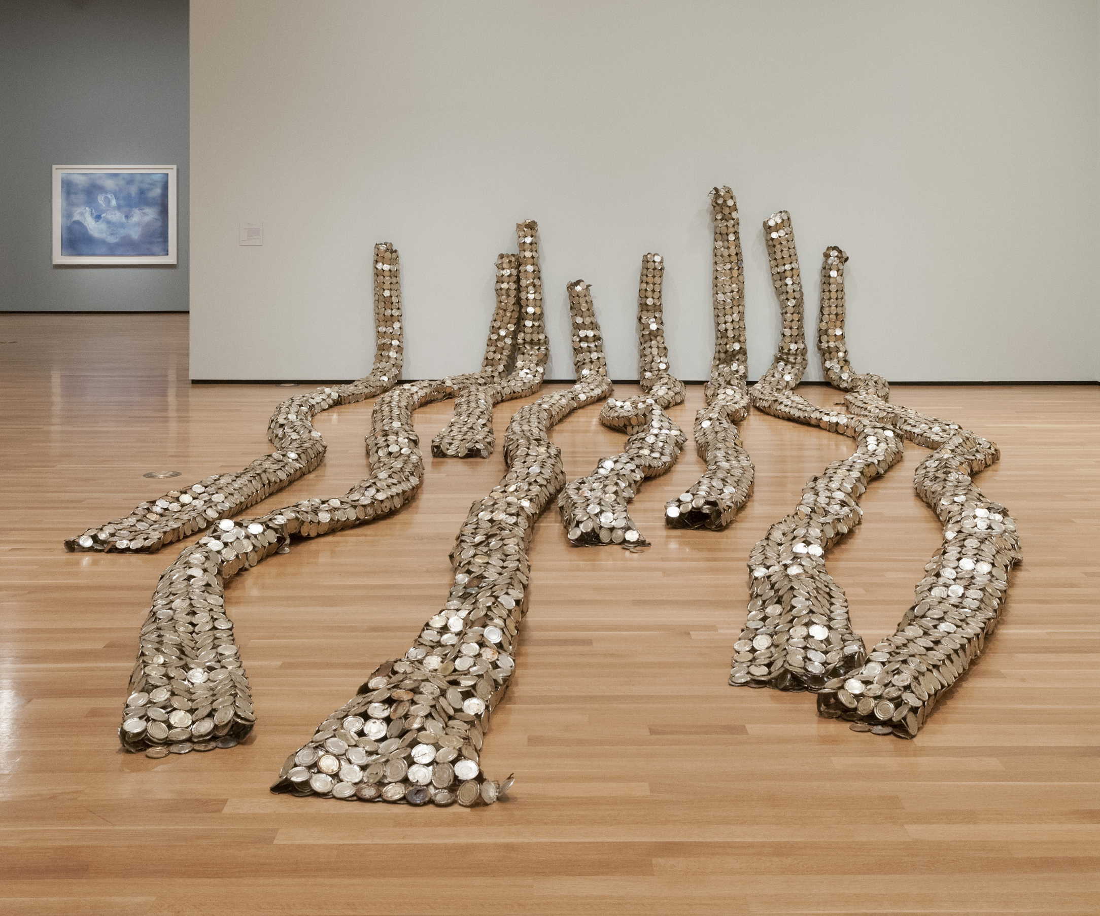 Sheets of linked milk tin lids were rolled into long, cylindrical forms to make Anatsui's Drainpipe (2010).