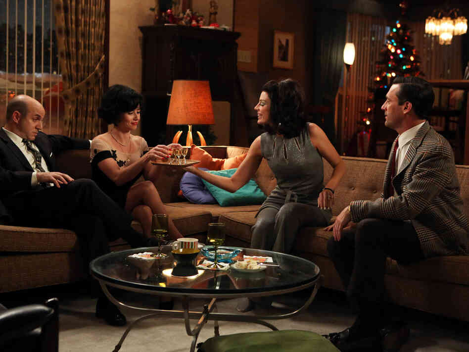 Dr. Arnold Rosen (Brian Markinson) and Sylvia Rosen (Linda Cardellini) celebrate New Year's Eve with Megan Draper (Jessica Pare) and Don Draper (Jon Hamm) as the sixth season of Mad Men opens.