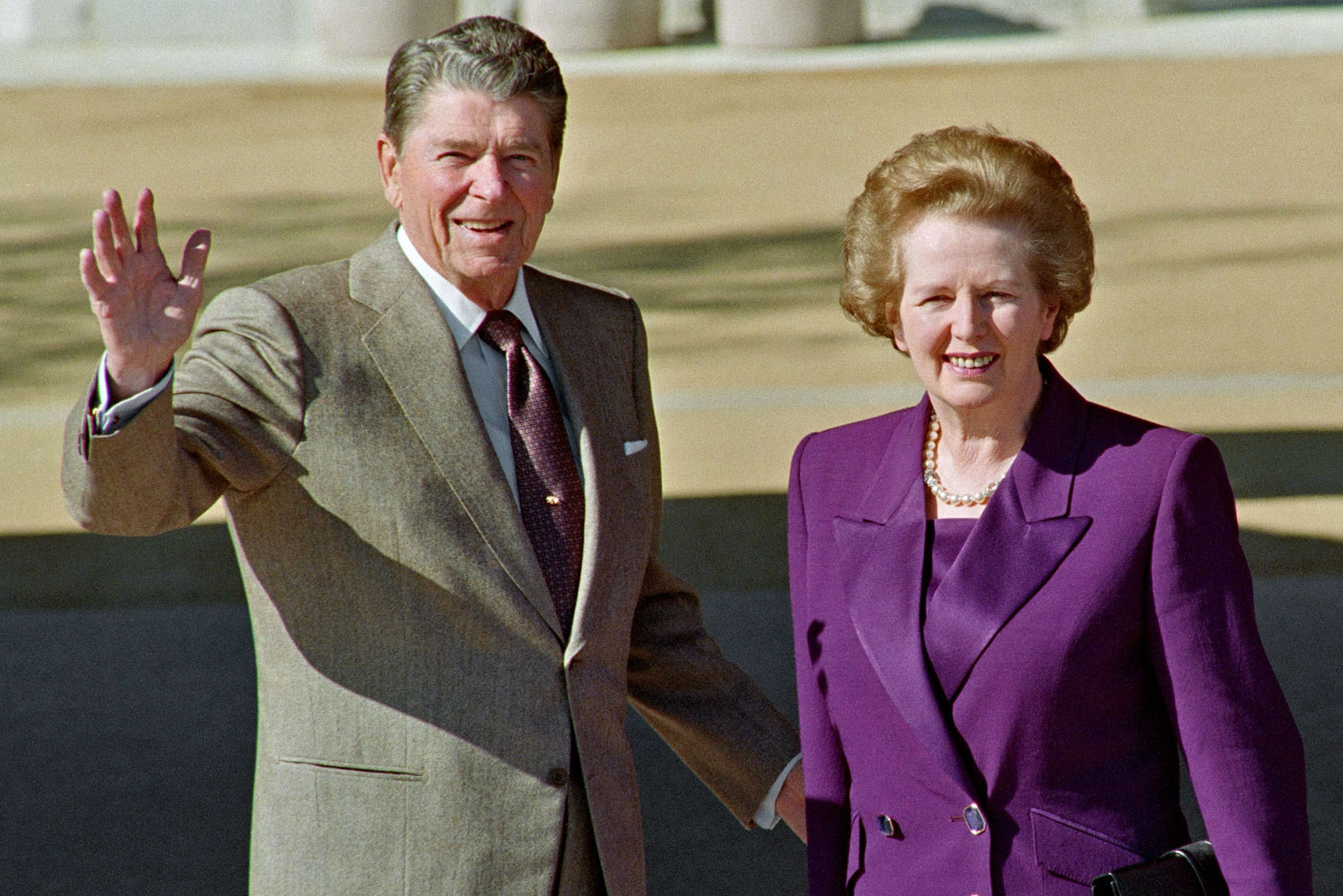 Former U.S. President Ronald Reagan waves as he greets next to former British Prime Minister Margaret Thatcher as she arrives to visit him at Reagan Library, on February 4, 1991.