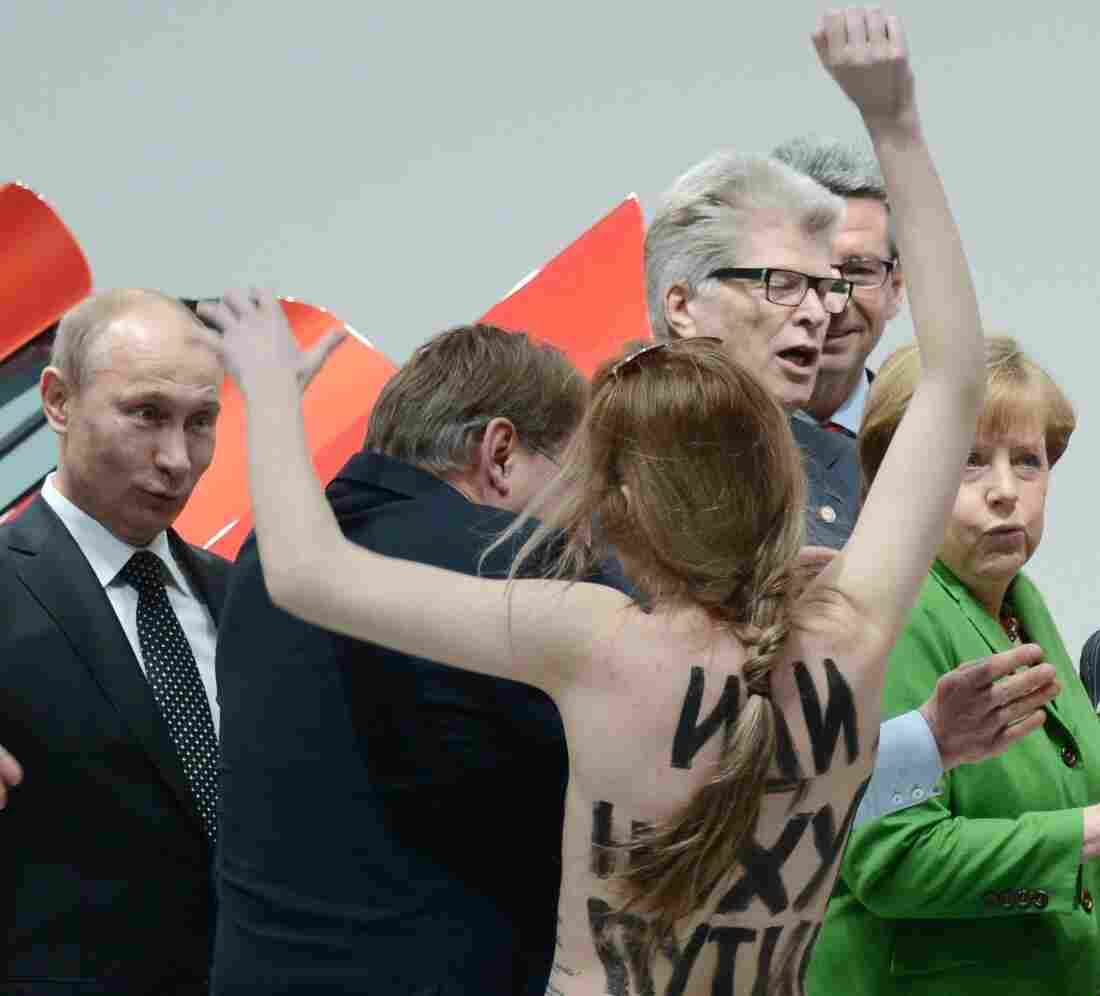 Russian President Vladimir Putin (far left) looks on Monday in Hanover, Germany, as one of three women who stripped off their tops protests his appearance at a trade fair. German Chancellor Angela Merkel is in the green jacket.