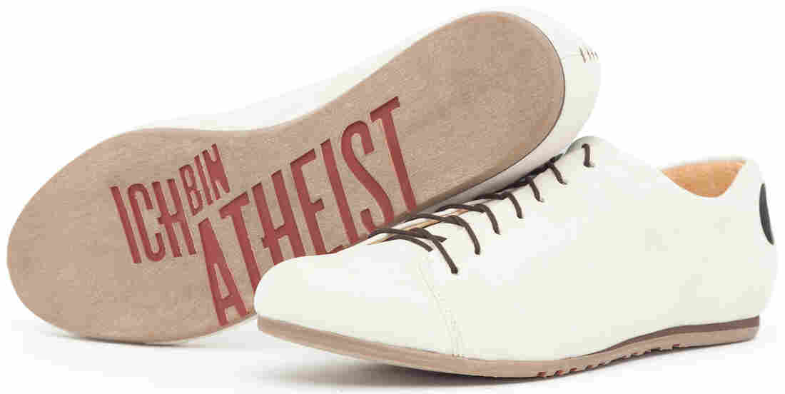 "White shoes with the writing ""ich bin atheist"" on the sole"