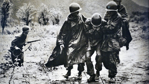 In this copy of a photograph on display at Kapaun Mt. Carmel Catholic High School in Wichita, Kan., a wounded soldier is helped by Army chaplain Emil Kapaun (on the soldier's left) during the Korean War. The Kansas native died a prisoner of war in 1951.