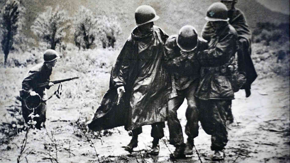 In this copy of a photograph on display at Kapaun Mt. Carmel Catholic High School in Wichita, Kan., a wounded soldier is helped by Army chaplain Emil Kapaun (on the soldier's l