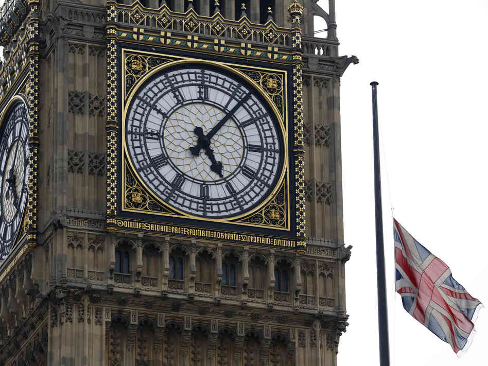 A Union flag flies at half staff over the Houses of Parliament, an