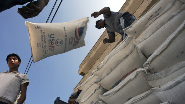 Palestinians unload bags of flour donated by USAID, or the United States Agency for International Development, at a depot in the West Bank village of Anin in 2008. (AP)