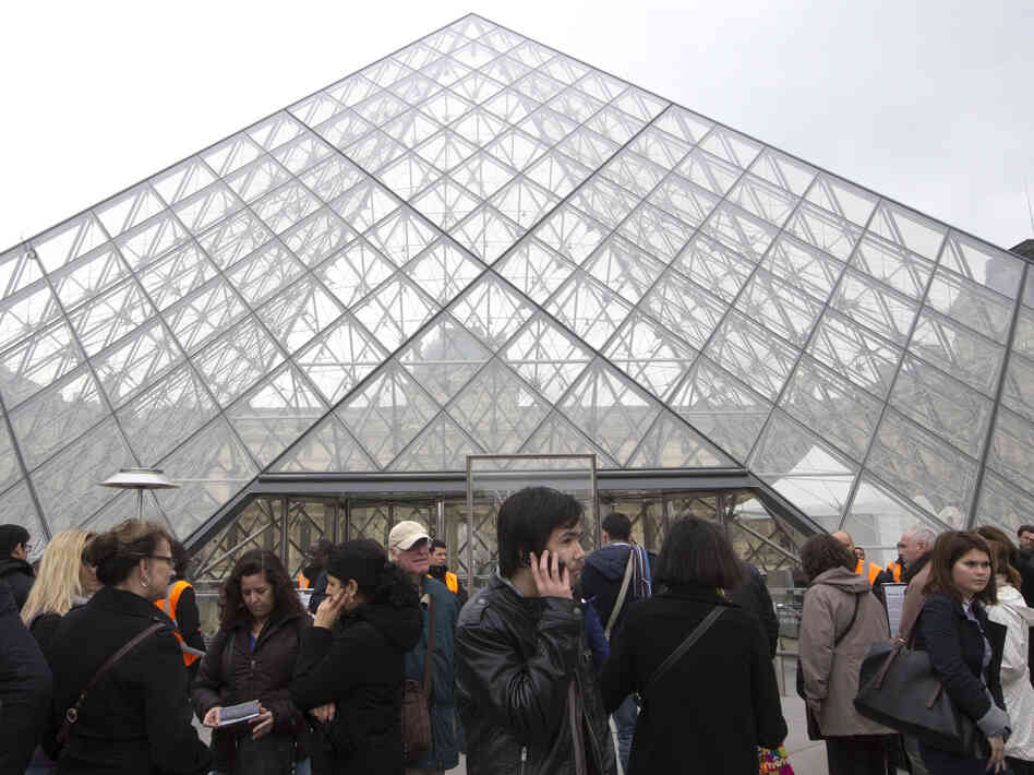 Visitors stands in front of the entrance to the Louvre in Paris, on Wednesday. The museum was closed for the day after workers walked off t