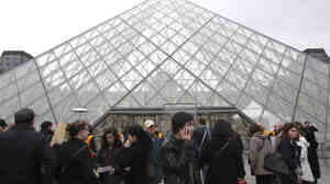 Visitors stands in front of the entrance to the Louvre in Paris, on Wednesday. The museum was closed for the day after workers walked off the job to protest what they say is the increasing problem of pickpockets in the museum's vast galleries.