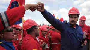 Venezuela's acting president, Nicolas Maduro, fist-bumps a worker of the state-run oil company, Petroleos de Venezuela, S.A., last month. Maduro faces opposition candidate Henrique Capriles in Sunday's presidential election. Whoever wins will have to tackle the legacy of Chavez's oil programs.