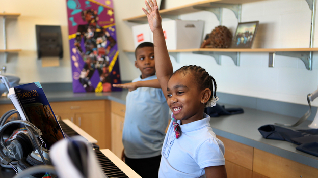 Jionni Anderson is a third grader at Savoy Elementary School. Anderson raises her hand to answer a question in Mr. Scott's keyboard class. (NPR)