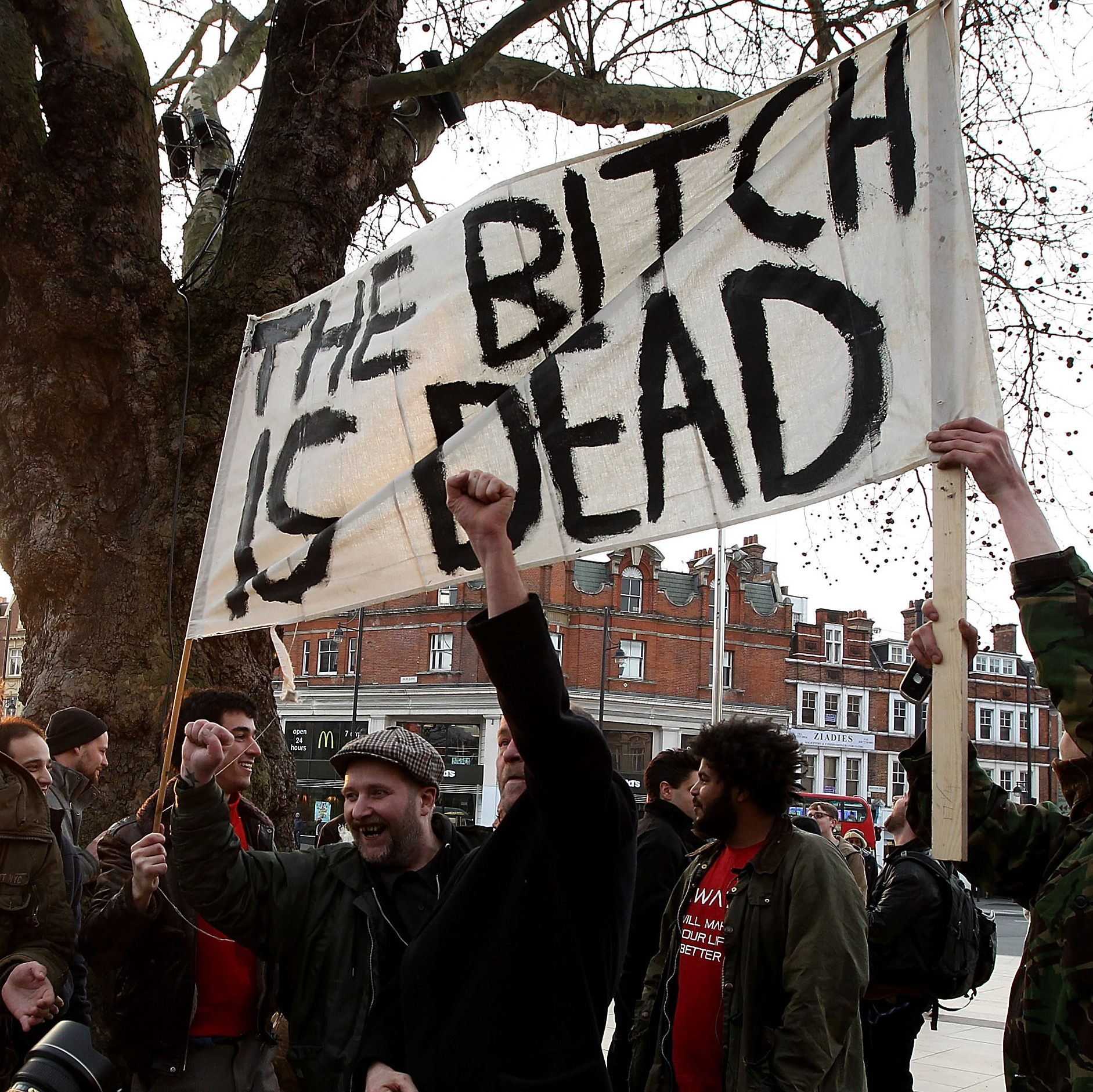 People hold banners Monday celebrating Thatcher's death in the London neighborhood of Brixton.