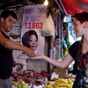 Tatiana Coelho buys fruit from a vendor in a favela in Rio de Janeiro, Brazil, on Sept. 20, 2012. Prices, especially for food, are skyrocketing in Brazil.