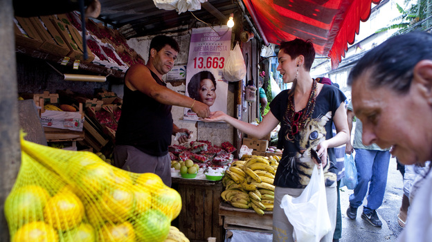 Tatiana Coelho buys fruit from a vendor in a favela in Rio de Janeiro, Brazil, on Sept. 20, 2012. Prices, especially for food, are skyrocketing in Brazil. (Christian Science Monitor via Getty Images)