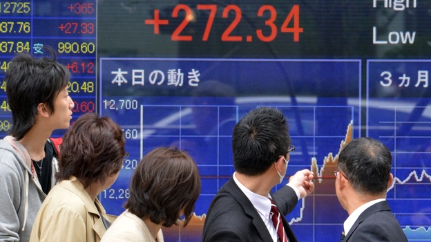 Passersby watch share prices spike in Tokyo on April 4, the day Japan's central bank announced a massive purchase of government bonds. The bank hopes the scale of the effort will boost Japan's slow-moving economy. (AFP/Getty Images)