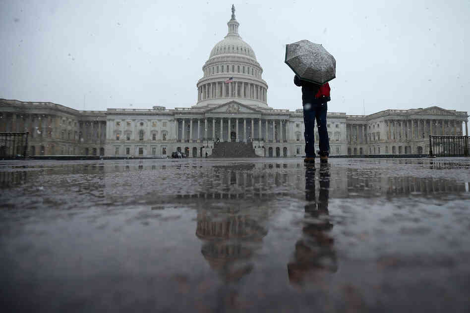 A tourist takes cover underneath an umbrella while snapping a photo of the U.S. Capitol on March 6, 2013 in Washington, DC.