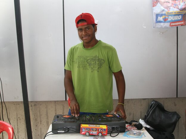 Alvaro Perez volunteers as a DJ at a socialist party stand in Caracas, Venezuela, playing songs in support of candidate Nicolas Maduro.