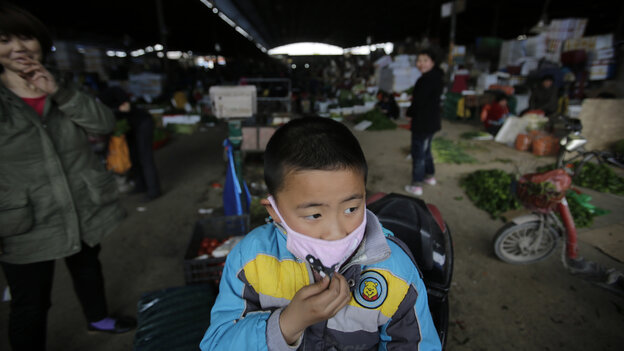 A child wears a mask near a closed section of a poultry market in Shanghai, where health workers detected the new bird flu, H7N9.