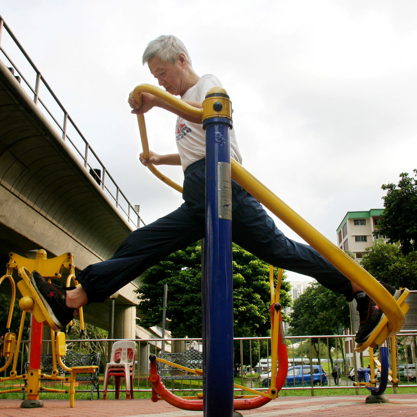 An elderly man exercises on a stretching device in Singapore, in 2005.