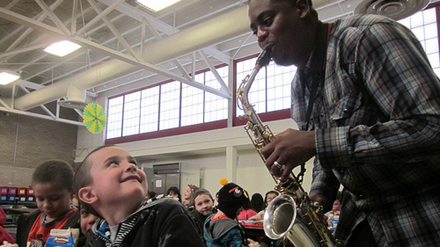Saxophonist Harold Rapp plays during lunchtime at Alice Terry Elementary School in Sheridan, Colo. (Jenny Brundin for NPR)
