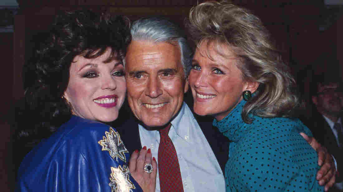 Joan Collins, John Forsythe and Linda Evans at a party celebrating the production of 150 episodes of Dynasty in 1986.