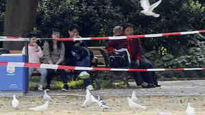 People sit near pigeons at a park in Shanghai Sunday. A new strain of bird flu has spread from eastern China to other provinces, with 13 deaths reported.