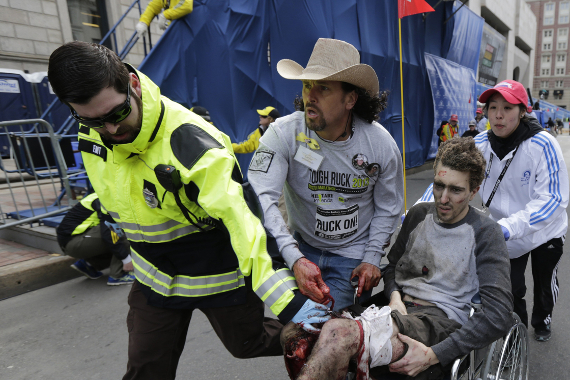 Medical responders run an injured man past the finish line.