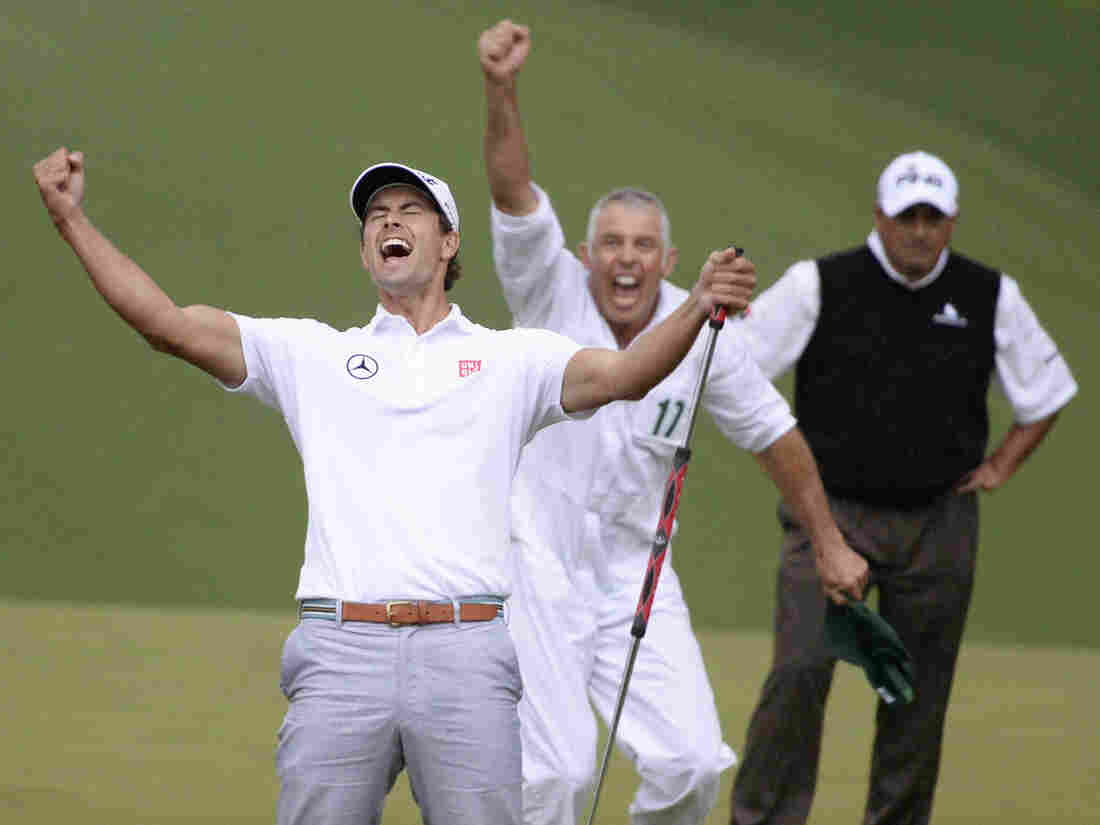 Adam Scott (left) of Australia celebrates after winning a playoff against Angel Cabrera (right) of Argentina at the Masters golf tournament in Augusta, Ga. In between them is Steve Williams, Scott's caddie.