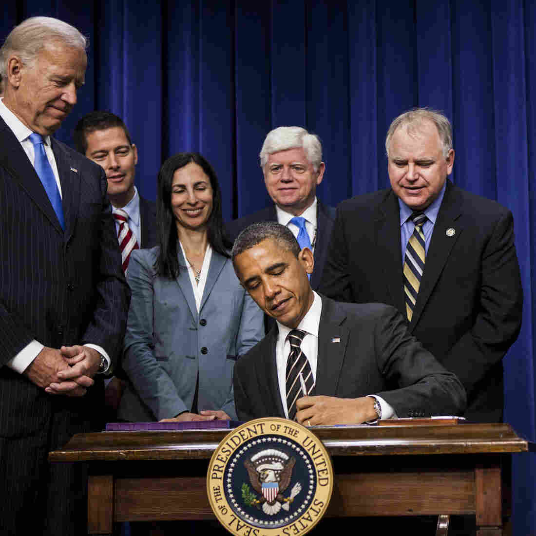 Vice President Biden and members of Congress watch as President Obama signs the STOCK Act on April 4, 2012. A year later, Congress moved to undo large portions of the law without fanfare.