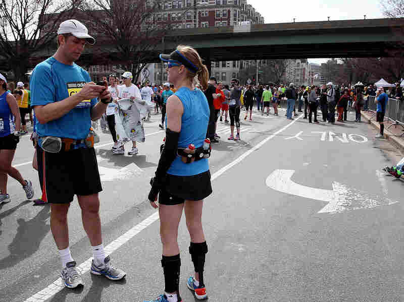 A runner uses his cellphone after two bombs exploded at the Boston Marathon on Monday.