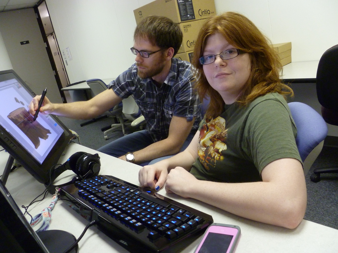 two young people working on a computer with a stylus pen