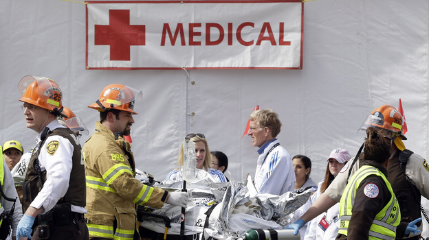 Medical personnel work outside the medical tent in the aftermath of two explosions near the finish line of the Boston Marathon on Monday. At area hospitals, doctors say they were confronted with the kinds of injuries U.S. troops get in Iraq and Afghanistan. (AP)