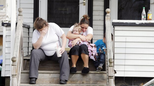 Neighbors sit outside the house of Krystle Campbell's parents in Medford, Mass., on Tuesday. Campbell was killed in the explosions at the finish line of the Boston Marathon on Monday. (AP)