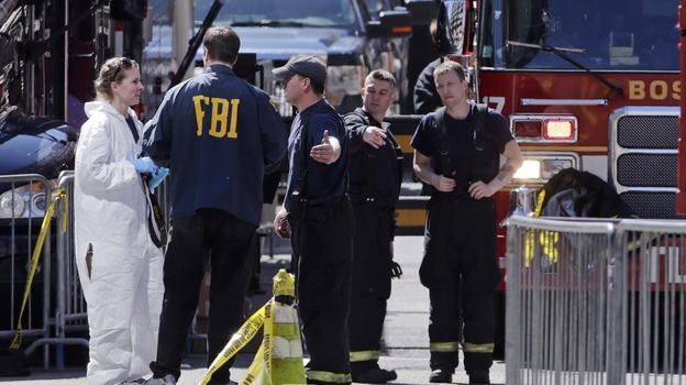 Boston firefighters talk with FBI agents and a crime scene photographer Tuesday at the scene of the Boston Marathon explosions. (AP)