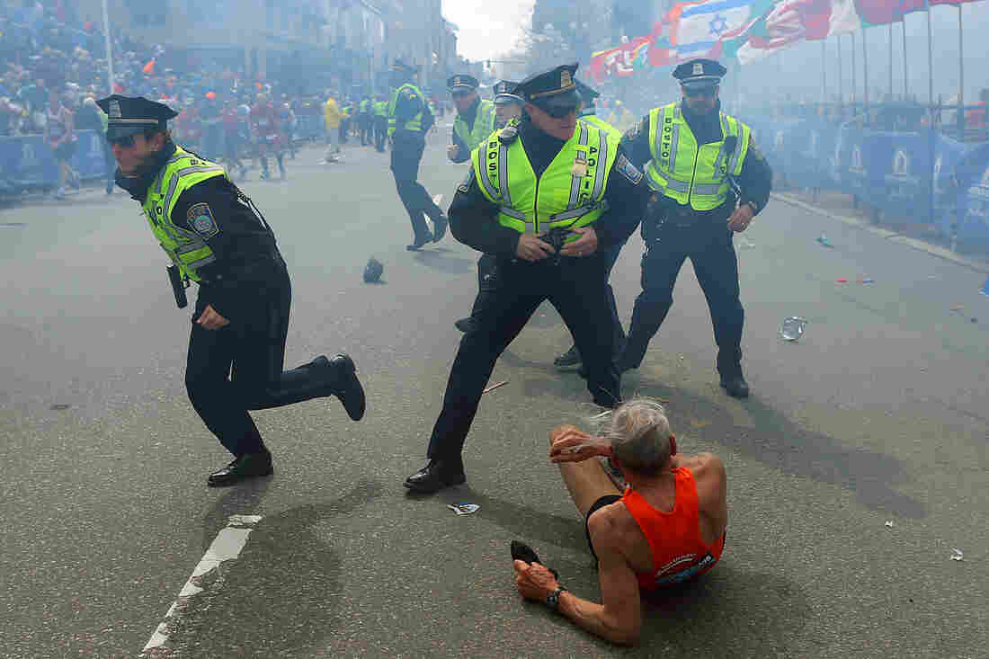 Police officers with their guns drawn hear a second explosion down the street near the finish line of the Boston Marathon. The first explosion knocked down a runner at the finish line.
