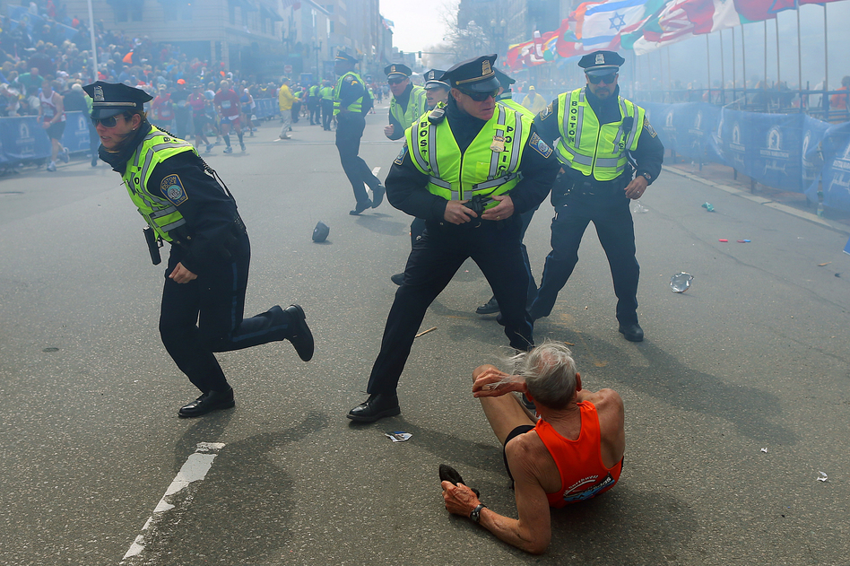 Police officers with their guns drawn hear a second explosion down the street near the finish line of the Boston Marathon. The first explosion knocked down a runner at the finish line. (John Tlumacki/Boston Globe via Getty Images)