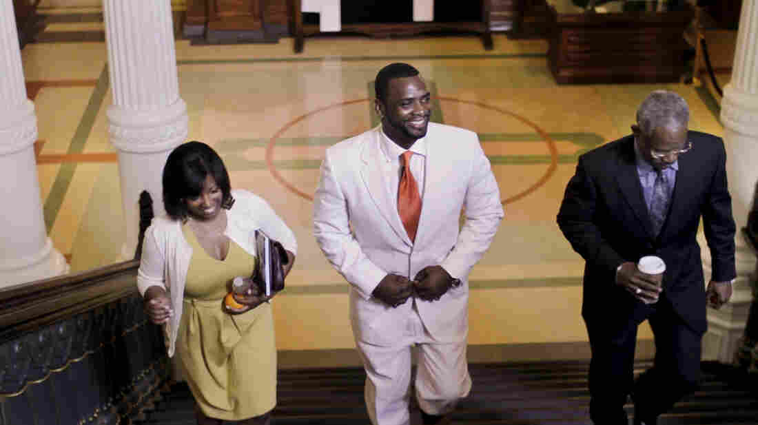 Dallas exonerees Christopher Scott (center) and Richard Miles, accompanied by Scott's girlfriend, Kelly Gindratt, prepare to be honored in the state Capitol in Austin, Texas, in March.